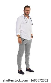 Serious handsome male doctor is standing relaxed with hand in pocket and looking at camera. Full length studio shot isolated on white.