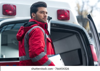 serious handsome male paramedic standing and looking away