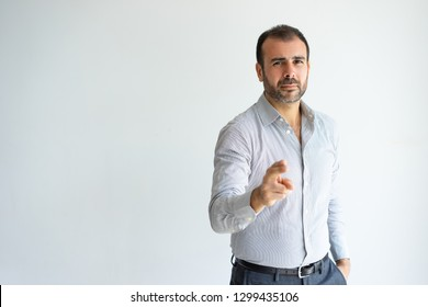 Serious handsome man pointing at you and looking at camera. Middle-aged guy choosing viewer or advertising something. Promotion concept. Isolated front view on white background.