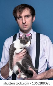 serious handsome man in shirt, suspender and pink bow tie looking at camera and holding adorable grey cat on blue background