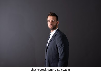 A serious handsome young businessman in a suit standing in front of a dark grey background in a studio.
