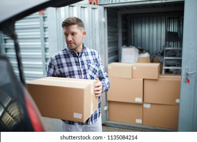 Serious handsome young man in casual clothing finding place in car for cardboard box while loading automobile at container storage area, he storing things in container