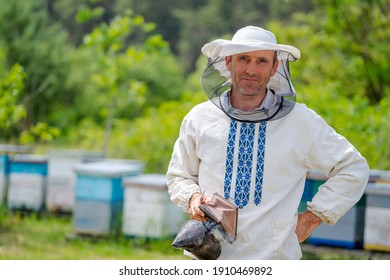 Serious hard working beekeper poses to the camera at apiary. Man with bee smoker in hands. Apiculture concept.