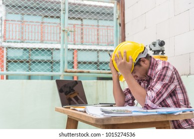 Serious hardworking unhappy man architect engineer busy working on big project at construction office desk with laptop and building plans