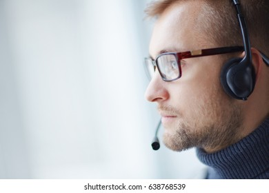 Serious helpdesk manager in eyeglasses listening to client problem in headphones