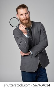 Serious hipster business man with beard and mustashes in suit holding magnifying glass and looking at camera, over grey background