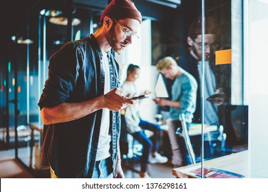 Serious hipster guy in casual wear sending text messages via mobile phone spending time in office, skilled male employee checking mail on smartphone  standing at coworking space during job process