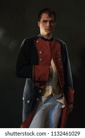 Serious historical regency man holds hand in jacket.