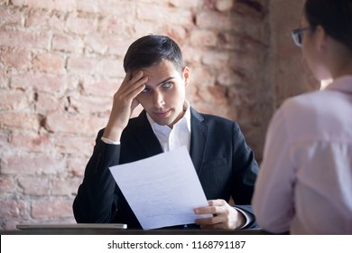 Serious HR manager interviewing young woman student in the office. Suspicious male wearing suit holding curriculum vitae and looking at applicant with disbelief, dissatisfied, bad first Impression