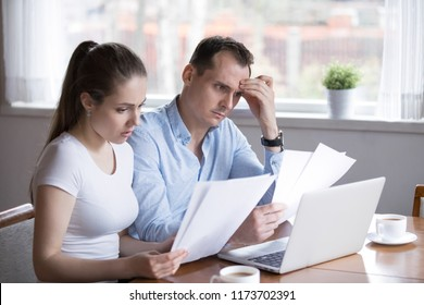 Serious husband and wife reading paper documents analyzing house utility bills, stressed couple get bank notice considering contract terms and conditions, man and woman managing paperwork and finances
