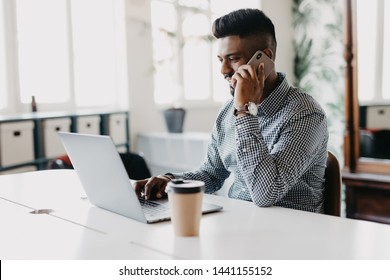 Serious Indian businessman sitting at the table in front of laptop computer and talking on mobile phone at office