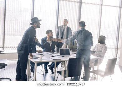 Serious Indian CEO in interacting with multiracial vendors at corporate meeting, explaining development project strategy, proving them to continue cooperation.