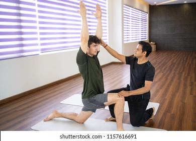 Serious Indian instructor helping beginner at yoga class. Man doing warrior pose in gym. Personal yoga instructor concept.