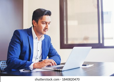 Serious Indian man working on laptop computer in the office alone