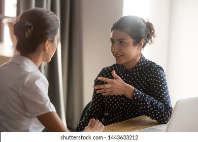 Serious indian mentor teacher worker talk to female colleague teach intern discussing new skills learning sit at work desk, two diverse coworkers work together help cooperate on project in teamwork