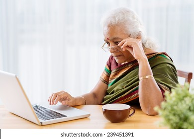 Serious Indian woman reading something on the laptop screen