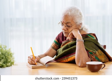 Serious Indian woman writing or sketching something in the notebook