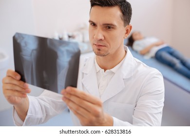 Serious intelligent doctor looking at the X ray photo