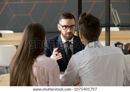 Serious investment broker, financial advisor or bank worker in suit and glasses consulting young couple giving legal advice, offering loan or presenting insurance services convincing to make deal