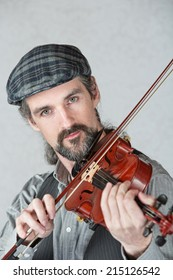 Serious Irish man playing a fiddle over gray background