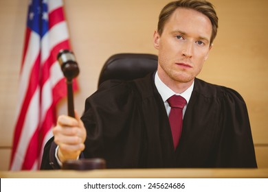 Serious judge about to bang gavel on sounding block in the court room