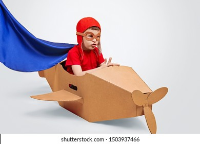 Serious kid in pilot helmet and superhero cape sitting at handmade cardboard airplane and playing over white background