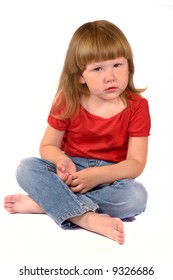 Serious kid sitting on the floor isolated on white