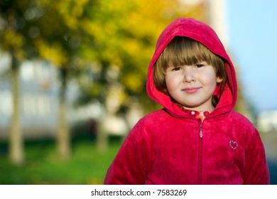 Serious kid standing outside in sunset lights