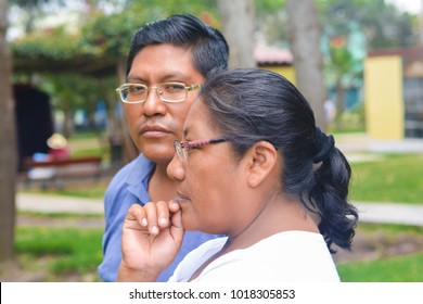 Serious latin man and woman wearing glasses.