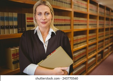 Serious lawyer holding a file while standing in library