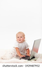 A serious little baby girl sits in front of a laptop surrounded by scattered dollars on a white background, a copyspace. High quality photo
