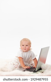 A serious little baby girl sits in front of a laptop surrounded by scattered dollars on a white background, a copyspace.