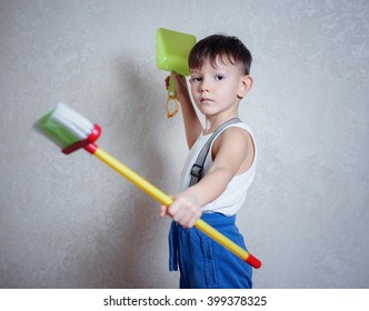 Serious little boy in blue slippers, pants, suspenders and tee shirt holding brooms across his chest in tough pose