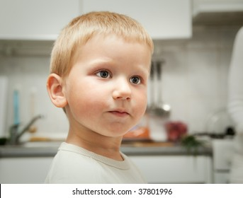 serious little boy standing in a kitchen
