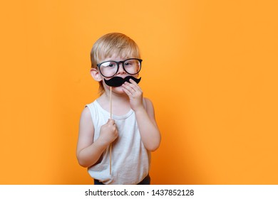serious little boy in a white t-shirt and black glasses put a mustache on a stick on his face to make him look older.