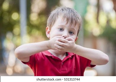 Serious little Caucasian boy closing his mouth with hands. Illustrative image for childhood trauma, child traumatic experience. Psychological assistance, children rescue. Silent cry for help. Stutter