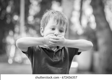 Serious little Caucasian boy closing mouth with hands. Asperger syndrome, autistic child, autism, refusal, disorder, parent abuse, school bullying, aggression, silent, refuse, psychological problem