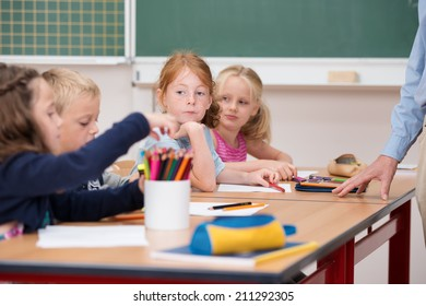 Serious little girl in class at school sitting with a group of classmates at a table watching them with a pensive expression