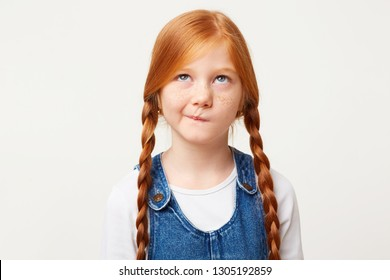 Serious little girl with freckles and braided in two long plaits red hair thinks, looks up incredulously, ponders about kindergarten, with doubt, one corner of the lips pursed, white background
