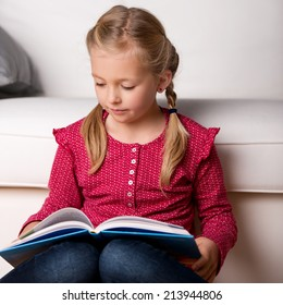 Serious little girl reading book in front of sofa at home