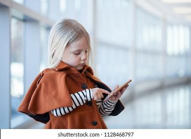 Serious little girl wearing orange coat playing smartphone