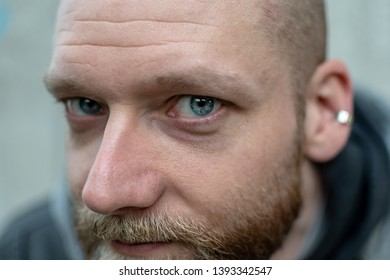 serious looking bearded man looks into the camera