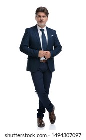 Serious looking businessman standing with his legs crossed while fixing his jacket and wearing a blue suit on white studio background