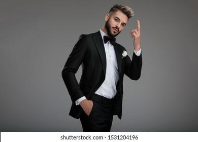 Serious looking groom holding a fired finger gun and dramatically walking away with his hand in his pocket on gray studio background
