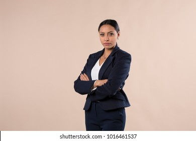 serious looking hispanic business woman with her arms crossed
