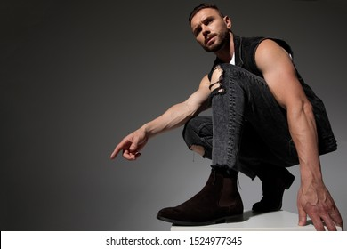 Serious looking man pointing to the side and squatting while wearing a black jeans vest on gray studio background