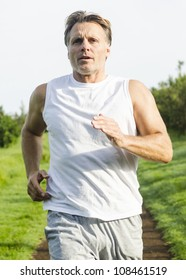 serious looking man running in park.
