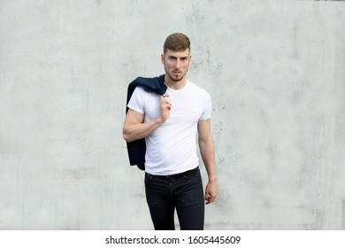 Serious looking man walking forward and staring ahead while he is holding his jacket over his shoulder on grey outdoor background