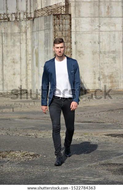 Serious looking man walking forward and looking straight to camera while wearing blue suit on raw industrial background.