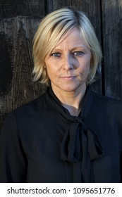 Serious looking, middle aged, Swedish woman wearing a black blouse, standing by a a rough, dar painted, wooden wall.